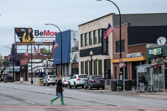 A woman walks across the northbound lanes of Woodward Avenue at 9 Mile Road in downtown Ferndale on Wednesday.
