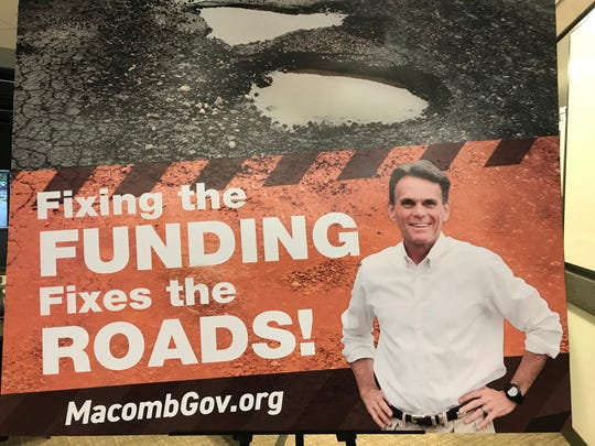 Macomb County Executive Mark Hackel displays this year's roadside billboard, which focuses on fixing roads, that will appear on the way to the Mackinac Policy Conference during a news conference May 22, 2019 in Mount Clemens.