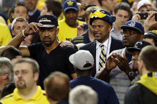 Former Michigan Wolverines players Juwan Howard and Jalen Rose greet Michigan fans as the watch the Wolverines play against the Louisville Cardinals during the 2013 NCAA Men's Final Four Championship at the Georgia Dome on April 8, 2013 in Atlanta, Georgia.