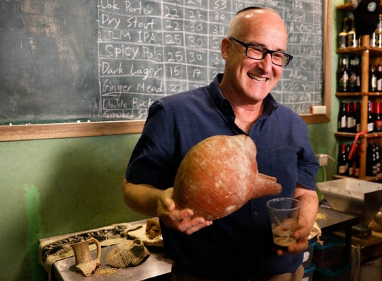 Prof. Aren Maeir, from Bar Ilan University, holds an ancient jar and a glass of beer during a press conference in Jerusalem, Wednesday, May 22, 2019.