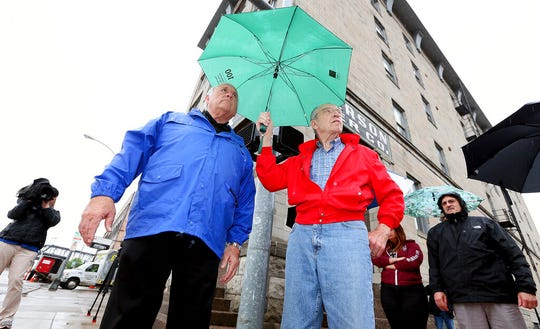 Davenport, Iowa Mayor Frank Klipsch, left talks to U.S. Sen. Chuck Grassley, R-Iowa, about businesses affected by flooding during a tour of the downtown Friday, May 17, 2019, as rain falls in Davenport, Iowa.