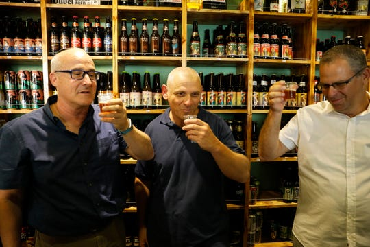 Prof. Aren Maeir, from Bar Ilan University, left, raises a toast with Dr Yitzchak Paz, from the Israeli Antiquities Authority, center, and Prof. Yuval Gadot, from Tel Aviv University during a press conference in Jerusalem, Wednesday, May 22, 2019.