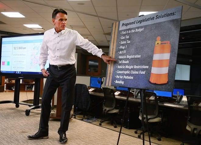 Macomb County Executive Mark Hackel points to a display with proposed legislative solutions for road repair funding during a press conference Wednesday at the Macomb County Communications and Technology Center in Mount Clemens.