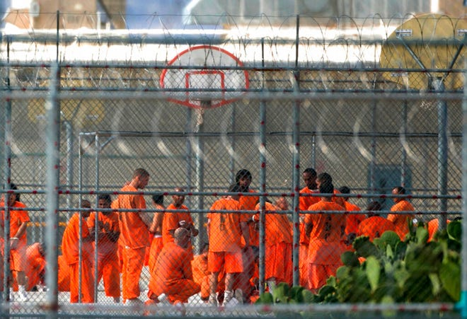 """In this July 4, 2015, file photo, prison inmates stand in the yard at Arizona State Prison-Kingman in Golden Valley, Ariz. A book that discusses the impact of the criminal justice system on black men is being kept out of the hands of Arizona prison inmates. The American Civil Liberties Union is calling on the Arizona Department of Corrections to rescind a ban on """"Chokehold: Policing Black Men."""""""