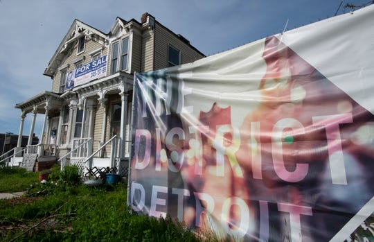 A dilapidated and unsold duplex sits amid parking lots and parking garages that surround Little Caesars Arena in the area known as 'The District Detroit.'