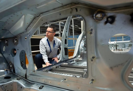 In this Tuesday, May 14, 2019 photo, Heiko Roesch, head of body construction, explains details of the new electric 'ID.3' car body during a press tour at the plant of the German manufacturer Volkswagen AG (VW) in Zwickau, Germany.