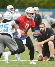 Lions QB Matthew Stafford, center, hands off to running back Theo Riddick during practice in Allen Park on Tuesday.