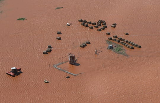 Hay bales and equipment are pictured in a flooded field, Tuesday, May 21, 2019, in Kingfisher, Okla. Flooding following heavy rains was an issue across the state.