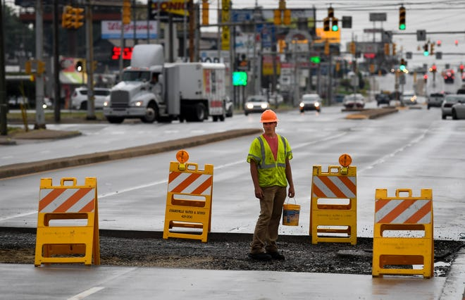 Bucket in hand, Jacob Sollman with paving contractor David Enterprises, works on repairing a section of South Green River Road, near Washington Square Mall, after a large sinkhole was created due to a water main break Wednesday, May 22, 2019.