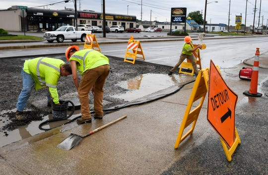 Workers with paving contractor David Enterprises Inc., left to right, Tim Mooney, Justin Weithmen and Jacob Sollman work to get the water out of the pavement cut so they can complete repairs on the section of South Green River Road, near Washington Square Mall Wednesday, May 22, 2019.