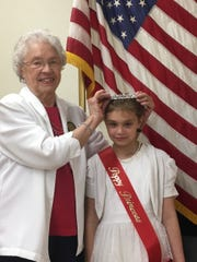 American Legion Auxiliary Unit 75 Poppy Chair Kathryn Curran crowns 2019 Poppy Princess RaeElla Mae Bremser ahead of Memorial Day.  Bremser, 8, is the daughter of Myke and Robyn Bremser and has been involved in the Auxiliary since birth.  Bremser looks forward to helping veterans in our community and wants to help little kids learn about our service men and women.  Bremser has worked with the Old Glory Honor Flights, helped with fundraisers and made many cards and rocks of thanks for our Veterans.  She plans to hide rocks for veterans to be found at Veterans Park after the Memorial Day Parade.