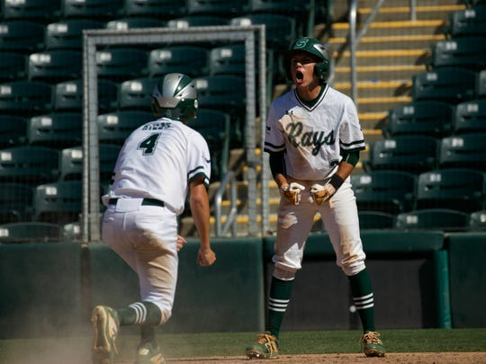 Jordan Martinez, right, of Seacrest Country Day School celebrates scoring runs with Matt Riley on Wednesday in the Class 2A state baseball semifinals against Wakulla Christian at Hammond Stadium in Fort Myers.