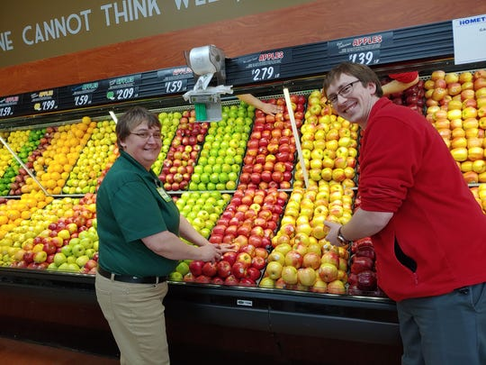 Alex Stodola, owner of Stodola's IGA, and produce manager Michelle Lelou stock the fruit shelves in the Luxemburg grocery store. Stodola's customers should be able to shop online with the system the store plans to implement early next year.