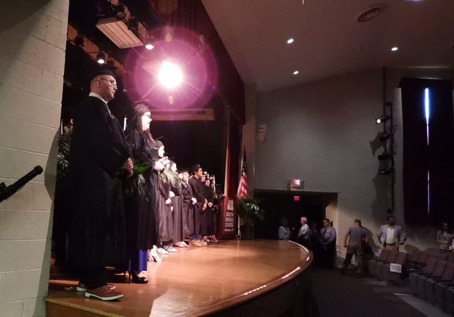 Central Academy graduates stand on stage for photos Tuesday evening during commencement ceremonies.