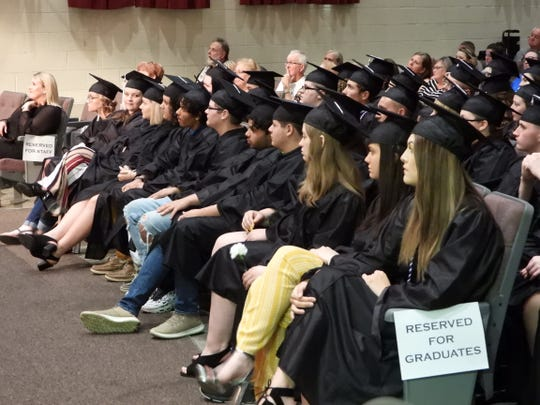 Central Academy graduates wait to get their diplomas Tuesday evening in Henderson.