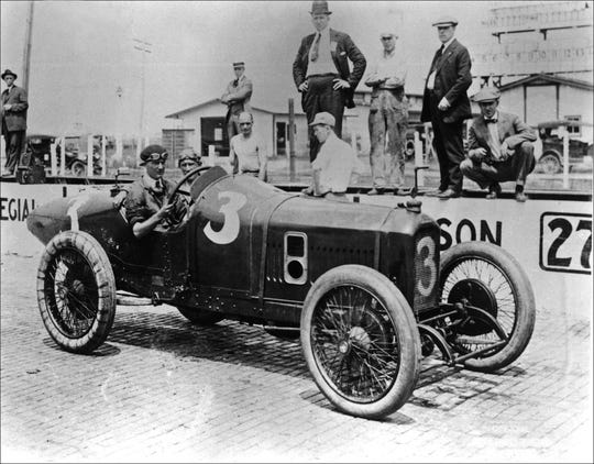 1919 Indy 500 winner Howdy Wilcox is shown behind the wheel of his #3 Peugeot. Others around the  car are unidentified
