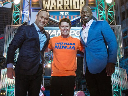 """American Ninja Warrior"" hosts Matt Iseman, left, and Akbar Gbajabiamila post with IndyCar driver Scott Dixon on Monument Circle in 2018. Iseman and Gbajabiamila will serve as co-grand marshals at this year's Indianapolis 500."