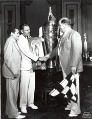 Louis Meyer. center, receives the Borg-Warner trophy after winning the Indianapolis 500 in 1936. He'd already  finished the milk at this point.