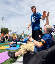 Indianapolis Colts' quarterback Andrew Luck greets people before reading to them at The Children's Museum on May 22, 2019.
