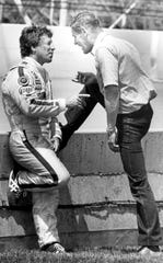 Bobby Unser, right, talks with 1969 winner Mario Andretti at the pit wall during practice at the Indianapolis Motor Speedway in Indianapolis in 1982.