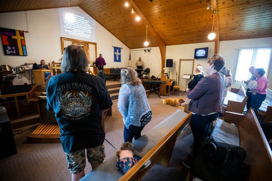 Members of the congregation and community members stand during the first annual blessing of the animals ceremony, Sunday, May 19, 2019, at Grace United Methodist Church in Tiffin, Iowa.