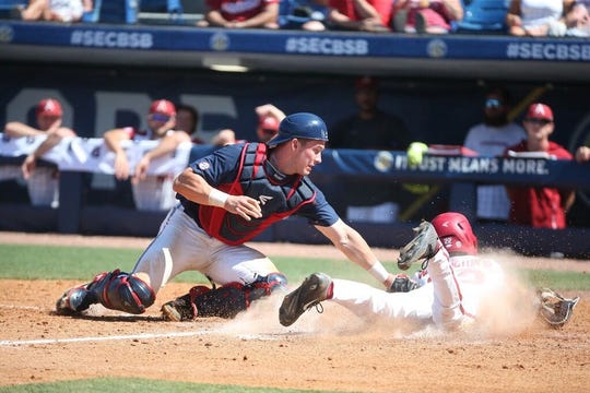 Ole Miss catcher Cooper Johnson attempts to tag an Arkansas runner in the 2019 SEC Tournament.