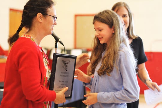 Amelia White receives The Winget Pen and Palette Award from Shannondale principal April Partin after teacher Melanie Ownby, right, listed many of Amelia's accomplishments. May 17, 2019