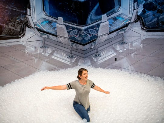 News Sentinel reporter Maggie Jones tries out the ball pit in a room dedicated to space conspiracies inside the National Enquirer Live attraction in Pigeon Forge on Wednesday, May 22, 2019.