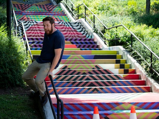 Ryan Wilusz slides down the bannister at the Weaving Rainbow Mountain mural, one of Knoxville's most Instagrammable spots.