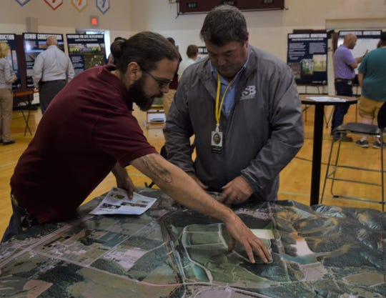 Frank Zultz, a Pike County resident, discusses the new nuclear waste disposal site at the now deactivated Portsmouth Gaseous Diffusion Plant with a DOE employee at a DOE open house Tuesday.