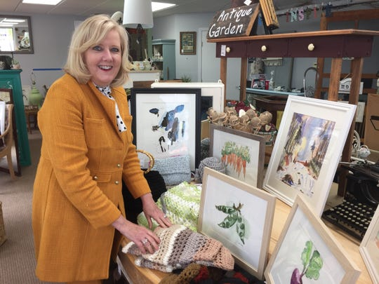 Watercolor artist and crocheter Vicki Lobodocky stands with some of her creations, Wednesday, May 22, 2019, at consignment shop Made 2 Inspire Resale Boutiques new location in downtown Howell.