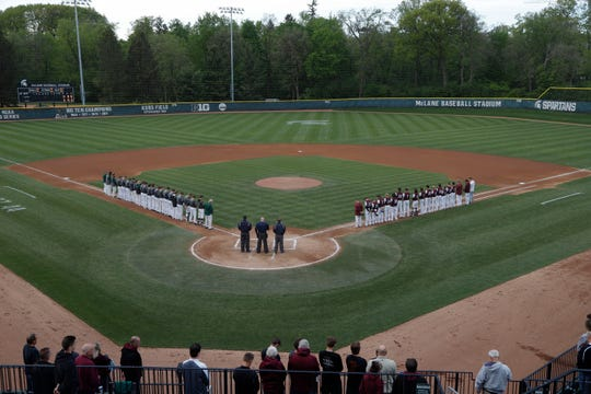 Players and fans stood Tuesday for a moment of silence before the Williamston-Eaton Rapids game at Michigan State University's  McLane Stadium to honor Ed Outslay. The longtime East Lansing High School assistant baseball coach died Monday.