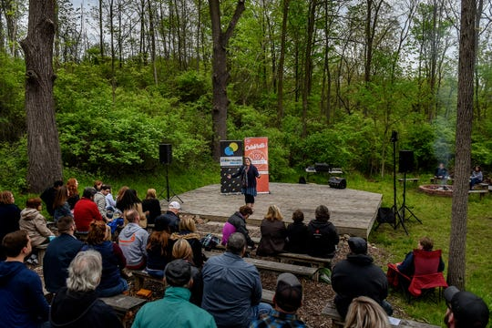 Maia Turek, a statewide recreation programmer, tells her story in front of the crowd at the Lansing Storytellers Project: 'Around the Campfire' event on Tuesday, May 21, 2019, at the Woldumar Nature Center in Lansing.