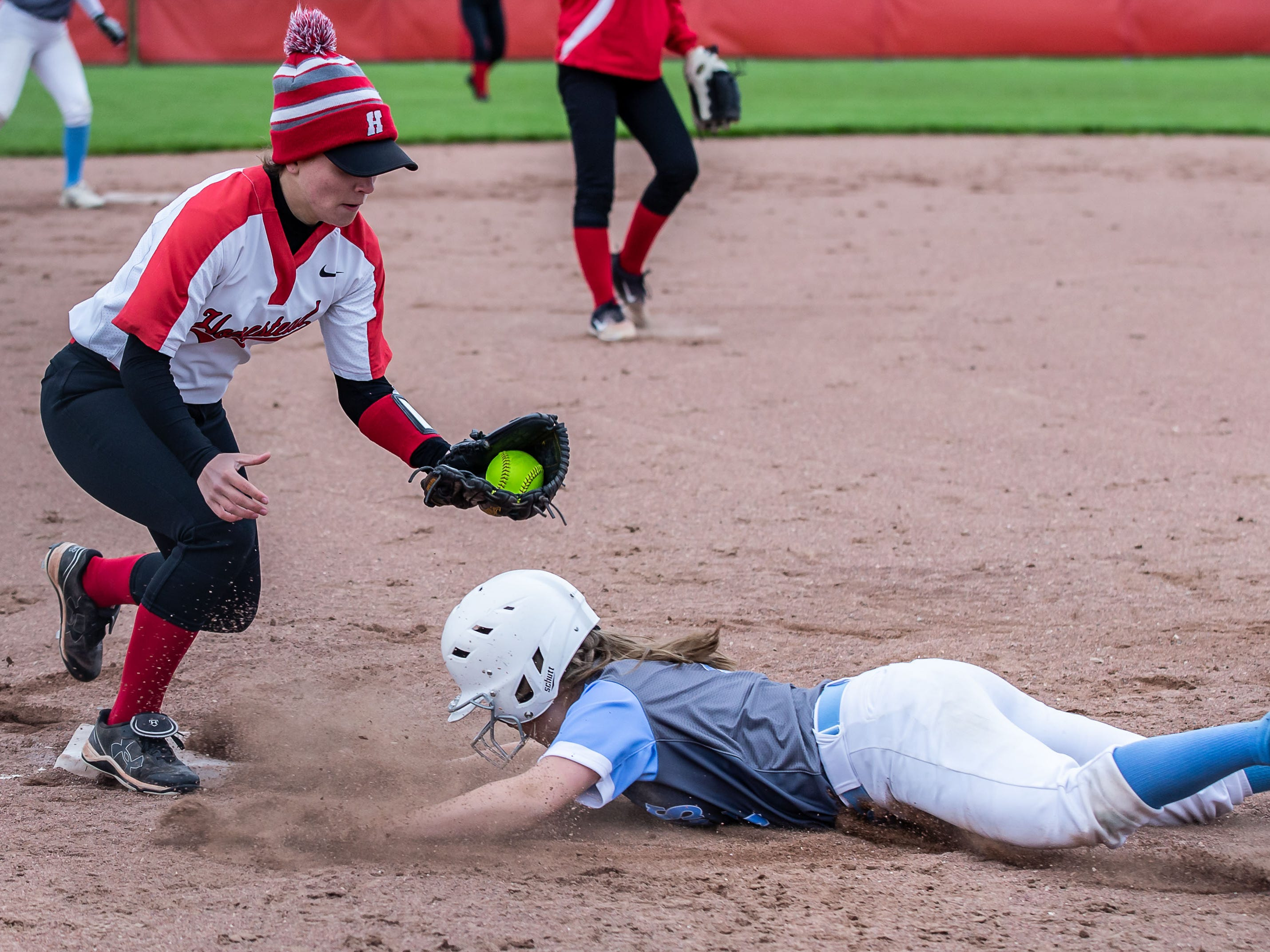 Brookfield Central's Ashley Dobrzynski (1) narrowly gets back to third base as Homestead's Cat Seiberlich (18) tries for the tag during the regional game at Homestead on Tuesday, May 21, 2019.