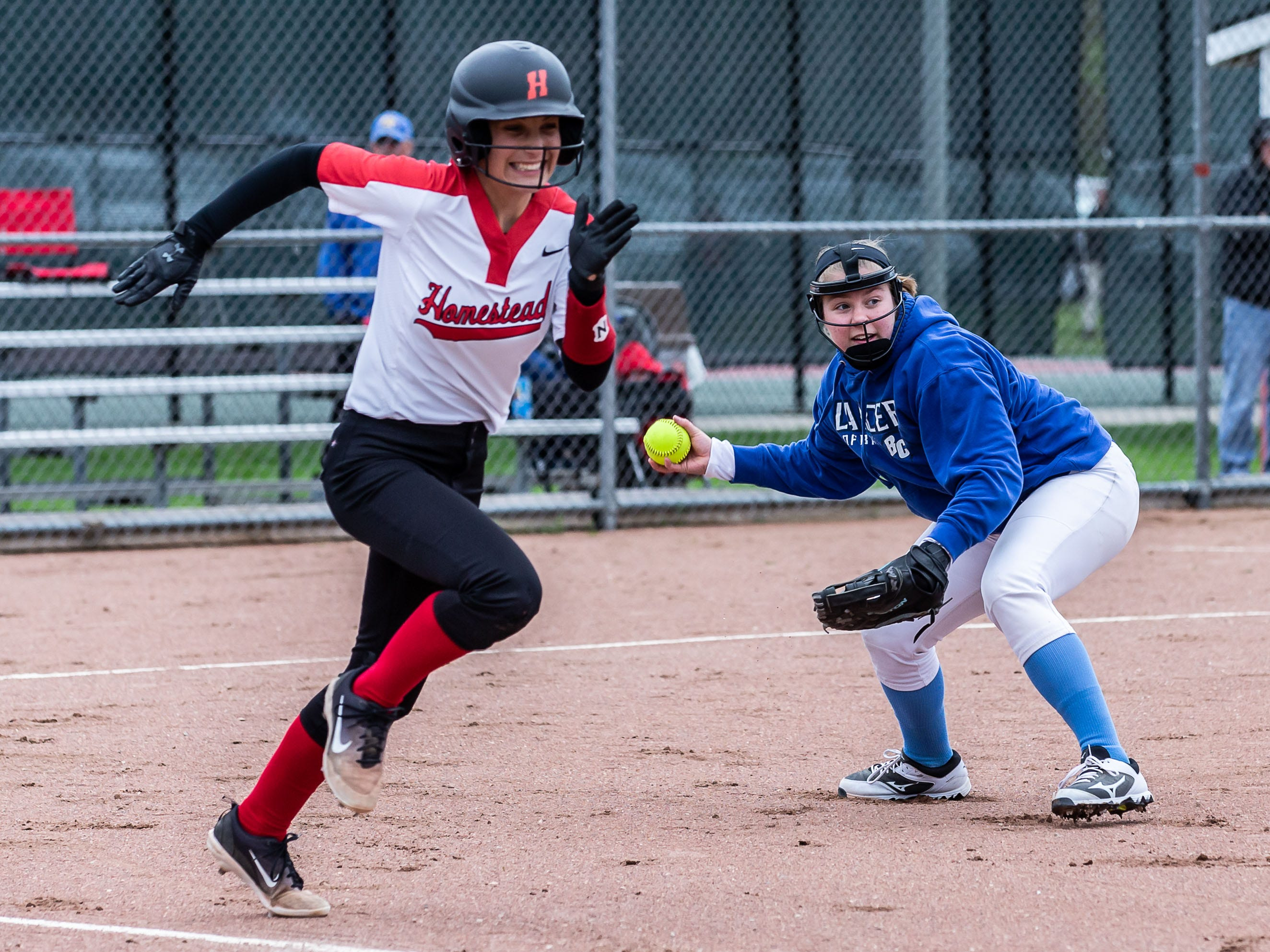 Homestead's Lauren Curtis (4) races for first as Brookfield Central first baseman Kate Burzynski prepares to throw her out during the regional game at Homestead on Tuesday, May 21, 2019.