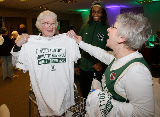 Resident Caroline Welles receives a Bucks T-shirt from Cindy Kaczmarowski as residents at St. Camillus enjoy a Bucks game watch party at this senior complex before the Bucks played the Toronto Raptors in the NBA Semifinals.