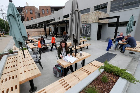 Ariel Powers of Milwaukee studies on the patio of Stone Creek Coffee's Downer Avenue. The coffee shop is among the 23 winners in this year's Mayor Design Awards.