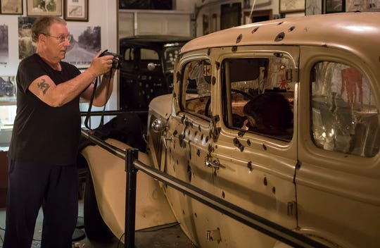 "Steve Bammann, from Pocono Lake, Penn., take a photo of the ambush car from the 1967 film ""Bonnie and Clyde"" on display at the Bonnie and Clyde Ambush Museum in Gibsland, La. on May 21. Thursday marks the 85th anniversary of the criminal couple's death just south of the town."
