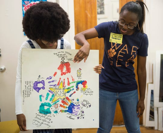 Visual art students Alanna Johnson, left, and Lexi Jenkins show off the ceiling tile they decorated at Booker T. Washington Magnet School at Hayneville in Montgomery, Ala., on Tuesday, May 21, 2019.
