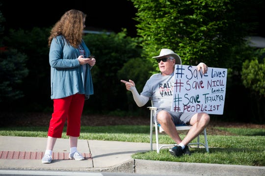 Michelle Richards (left) of Kingsport, Tennessee, and Gary Frady of Church Hill, Tennessee, protest outside Holston Valley Medical Center in Kingsport.