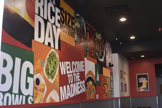 Teriyaki Madness is brightly decorated, including with pictures of food and bold catch-phrases like 'have a rice day,' and 'warning: food highly addictive.'
