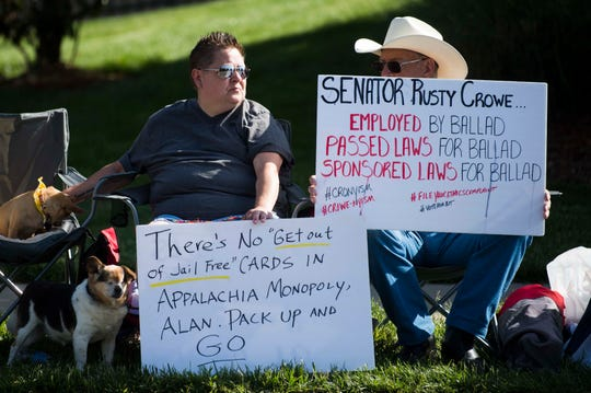Jamie Farris of Church Hill sits next to Earl Farris of Kingsport while protesting outside Holston Valley Medical Center on May 7.