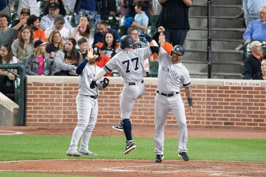 May 21, 2019; Baltimore, MD, USA; New York Yankees right fielder Clint Frazier (77) celebrates with  second baseman Gleyber Torres (25) and  center fielder Aaron Hicks (31) after hitting a three run home run in the fifth inning against the Baltimore Orioles at Oriole Park at Camden Yards. Mandatory Credit: Tommy Gilligan-USA TODAY Sports
