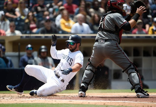 Greg Garcia #5 of the San Diego Padres scores ahead of the throw to Alex Avila #31 of the Arizona Diamondbacks during the second inning of a baseball game at Petco Park May 22, 2019 in San Diego, California.