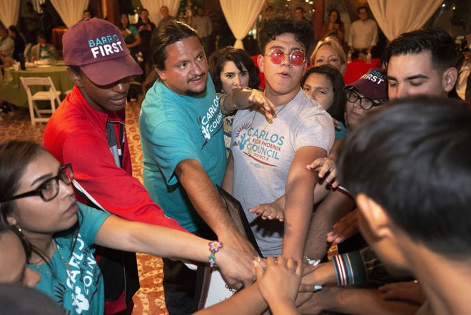 Carlos Garcia (left-center), a candidate for Phoenix City Council District 8, rallies with his volunteers at his election night party on May 21, 2019, at Corona Ranch in Phoenix.