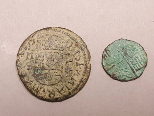 The reverse sides of the two Spanish coins found near Lake Powell, starting an archaeological investigation.
