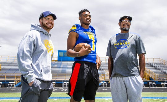 Tariq Jordan, middle, poses with his coach, Louie Ramirez, left, and his grandfather/guardian Cecil Jordan, right, on the field at the school.