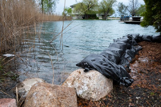 Sandbags are seen stacked along the edge of a canal in Harsens Island Wednesday, May 22, 2019. Harsens Island residents are being asked to reduce water consumption to prevent in preparation for rising water levels.