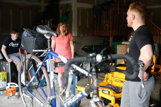 From left, Kyle and Cintdy Wilson observe  Ryan as he prepares his cycling equipment at their home in the Town of Poughkeepsie on May 20, 2019. Ryan has decided to ride this bicycle to Miami, Florida to raise money for ALS research.