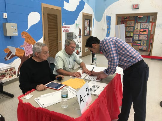 Josh Bardfield of Red Hook signs in to vote Tuesday at Mill Road Elementary School in the Red Hook Central School District. Election inspectors Jeff Hanna, left, and Jim Mort signed Bardfield in.